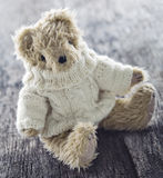Cute teddy bear. With a woolen sweater and balls of thread on vintage wooden background Stock Images