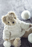 Cute teddy bear. With a woolen sweater and balls of thread on vintage wooden background Stock Photography
