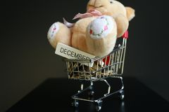 Christmas tree, coins in mini trolley isolated in dark black background. Cute teddy bear with word `December` written on wood stick on coins in mini trolley Royalty Free Stock Images
