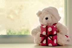 Cute teddy bears holding christmas gift box. And sitting in front of a rainy day window,vintage filter Stock Photo