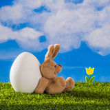 Cute teddy rabbit sitting at big egg and wait chick. Stock Images