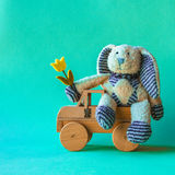 Cute teddy rabbit with yellow tulip on the wooden car. Stock Images