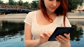 Cute teen age girl with ginger hair using her tablet outside near river. Outdoors lifestyle portrait. stock video footage