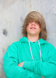 Cute Teen Boy. With shaggy blond hair and wearing a green sweatshirt standing against a cement wall with graffiti Royalty Free Stock Photos