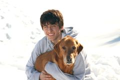 Cute Teen Boy with Dog in the snow. Teenage boy outdoor portrait in the snow with his Red Labrador Retriever Stock Photos