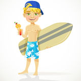Cute teen boy with a drink in a glass and a surfbo Stock Images