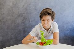 Cute teen boy eating salad. Cute teen boy dont like eating salad Stock Images