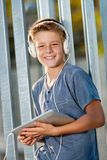 Cute teen boy holding tablet outdoors. Royalty Free Stock Images
