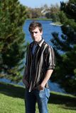 Cute teen boy at lake. Handsome teen boy standing in forest preserve Stock Photography