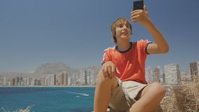 Cute teen boy makes video call on smartphone showing sights around on sea coast city skyline background.