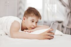 Free Cute Teen Boy With Brown Hair Is Lying On The Bed And Looking At The Phone. The Boy Holds The Phone In His Hand And Watches The Stock Image - 187791971