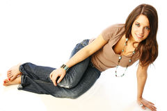 Cute teen in brown. Seventeen year old model Alex poses on floor in casual jeans and brown t-shirt Royalty Free Stock Photo