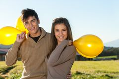 Cute teen couple outdoors with balloons.