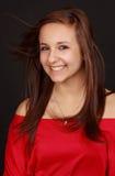 Cute teen girl. Portrait of a cute teen girl, red shirt, black background Stock Photo