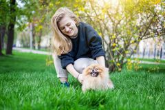 Cute teen girl with blond hair playing with her Pomeranian puppy. On green grass in the park Royalty Free Stock Image