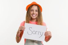 Cute teen girl character holding a sign with message sorry. On white background Royalty Free Stock Image