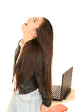 Cute teen girl by computer with her head back laughing Royalty Free Stock Photos