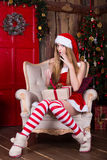 Cute teen girl getting a present near the. Christmas tree sitting in chair. New year surprise. Waiting for Santa Royalty Free Stock Photos