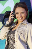 Cute Teen Girl with Headphones. In front of graffiti wall Royalty Free Stock Photography