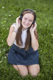 Cute teen girl in headphones enjoys the music on the green grass in park. Love of music. Royalty Free Stock Photos