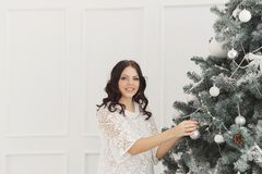 Teen girl decorates Christmas tree Stock Images