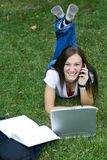 Cute teen girl laying down on the grass studying Stock Photo