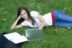 Cute teen girl laying down on the grass studying. With her laptop Royalty Free Stock Image