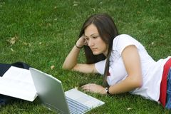 Cute teen girl laying down on the grass studying. With her laptop Royalty Free Stock Photography
