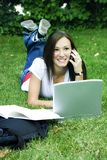 Cute teen girl laying down on the grass studying Royalty Free Stock Photography