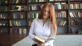Cute teen girl learn close up. Smart 20s blonde model read a literature turning pages of the book holding hands closeup. Shelves with books on background and stock video footage