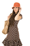 Cute teen girl model wearing a polka dot dress and orange hat Stock Images