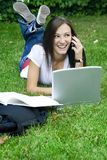 Cute teen girl on the phone. Cute teen girl laying down on the grass studying with her laptop Stock Photography