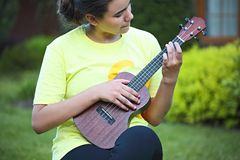 Cute teen girl playing her ukulele outdoors royalty free stock photo