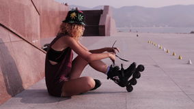 Cute Teen Girl Puts On Roller Skates At Seafront Stock Footage