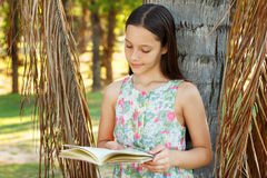 Cute teen girl reading book. Staying near tree, green grass in park. Selective focus Royalty Free Stock Photography