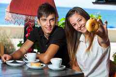 Cute teen girl showing donut at breakfast. Royalty Free Stock Image