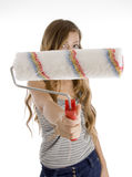 Cute teen girl showing painting brush. Cute teen girl showing roller painting  brush to camera on  an isolated white background Royalty Free Stock Photography