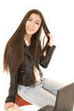 Cute teen girl sitting on the back of her school desk chair with Royalty Free Stock Images