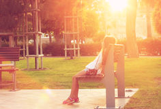 Cute Teen girl is sitting in the park at sunset Stock Photo