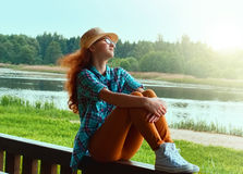 Cute teen girl sitting on the waterfront Royalty Free Stock Photos