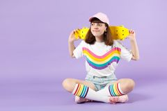 Cute teen girl in vivid clothes sitting, holding yellow skateboard looking aside isolated on violet pastel wall royalty free stock images
