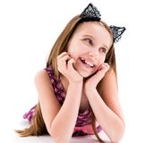 Cute teen girl wearing black cat ears. Cute teen girl wearing black laced ears of a cat, lying on the floor, smiling Stock Photography