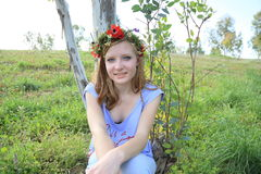 Cute teen girl with a wreath of spring flowers Stock Photos