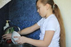 Cute teen girl 12-years old is washing dishes at kitchen. Close up Stock Image