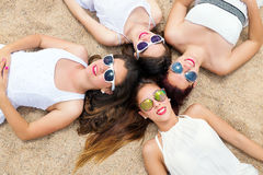 Cute teen girls joining heads together on sand. Portrait of foursome teen girlfriends laying on beach together and joining heads Stock Photos