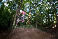 Cute teen jumping with his bike over a natural ramp in the fores. T Royalty Free Stock Photography