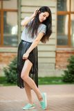 Cute teen posing near building. Cute young teen posing near building. sweet woman in a gray shirt and a black leather skirt walking around city. Concept of Stock Image