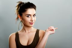 Cute teen woman pointing finger. Away.  on grey. Advertising presentation concept Royalty Free Stock Photography
