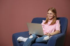 Cute teenage blogger with laptop sitting in armchair. Against color wall Stock Photos