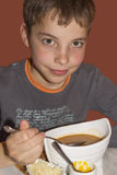 Cute teenage boy eating soup Stock Photos